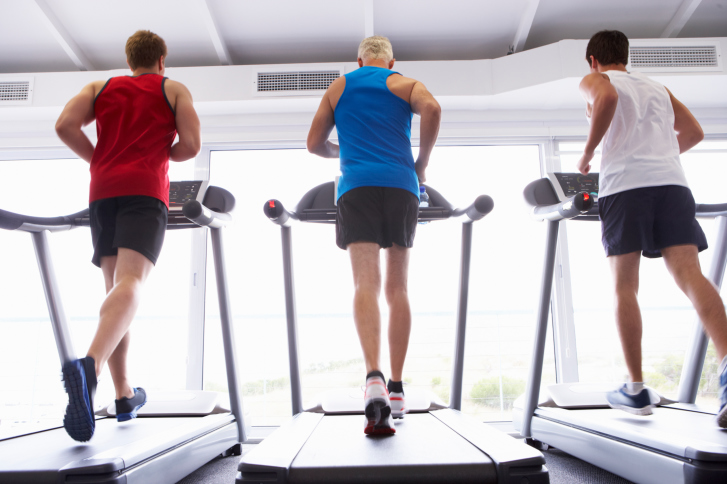 Back View Group Of Men Using Running Machines In Gym