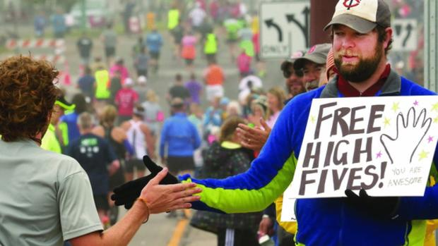 t06.21.2014 -- Steve Kuchera -- kucheraGMA0622c34 -- Mark Hutchins of Duluth gives out high fives and words of encouragement to Grandma's Marathon runners at the top of Lemon Drop Hill. Steve Kuchera / skuchera@duluthnews.com