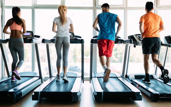 Picture of sporty people running on treadmill in gym